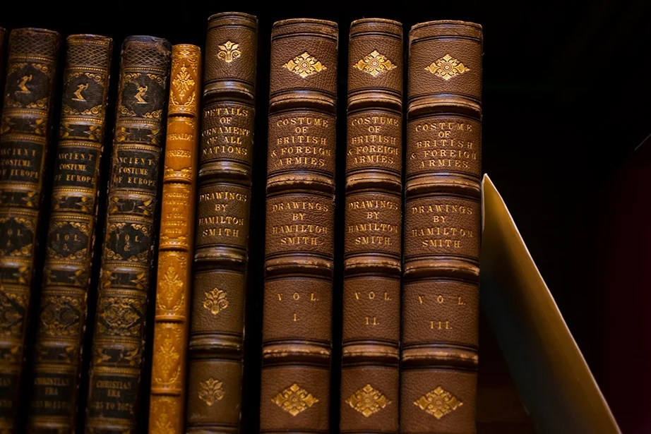 """Volumes of """"Costume of British & Foreign Armies"""" are part of the collection. The slip of white paper next to the books holds the place of a borrowed item."""