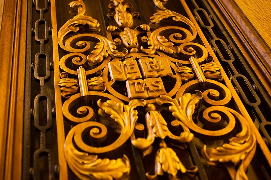 A Veritas shield adorns the entrance to the room.