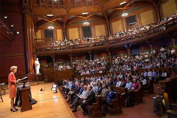 """""""We're here to build our IT community, to connect more closely to the University mission, and to learn from each other,"""" said Harvard CIO Anne Margulies (photo 1) during her opening remarks at the IT Summit at Sanders Theatre. Keynote speaker Professor Clay Christensen (photo 2) addressed online learning's transformation of higher education. """"What Harvard Business School needs to do is think about whether we can use online learning to help our customers-students. I think we can,"""" he said."""