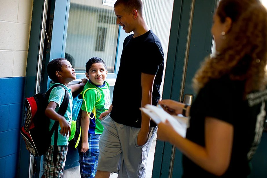 Jayden Melo (left) and Javier Ortiz warm up when they see that Cameryn Crowley has returned for another summer. Crowley, a camper since age 7, has moved through the ranks and now works as a junior counselor at South Boston Outreach Summer.