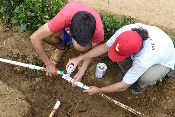 Volunteers from the Harvard chapter of Engineers Without Borders, William Jameson '16 and Christopher Lombardo of SEAS, work to repair a water pipe leak (photo 1) at the Dominican Republic site. A drill rig is sits at the location of the new water well (photo 2). Water from three local sources was tested in January: samples from the river, small wells called tinitas, and a spring near the top of a hill. The samples showed bacterial growth (left, photo 3). Water from the newly installed well, which was tested in August 2014, was free of bacteria (right).