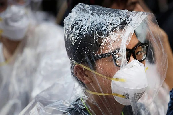A student pro-democracy protester covers his face in plastic wrap to guard against pepper spray in a standoff with police in Hong Kong on Monday. Protesters expanded their rallies throughout Hong Kong, defying calls to disperse in a major pushback against Beijing's decision to limit democratic reforms in the Asian financial hub.