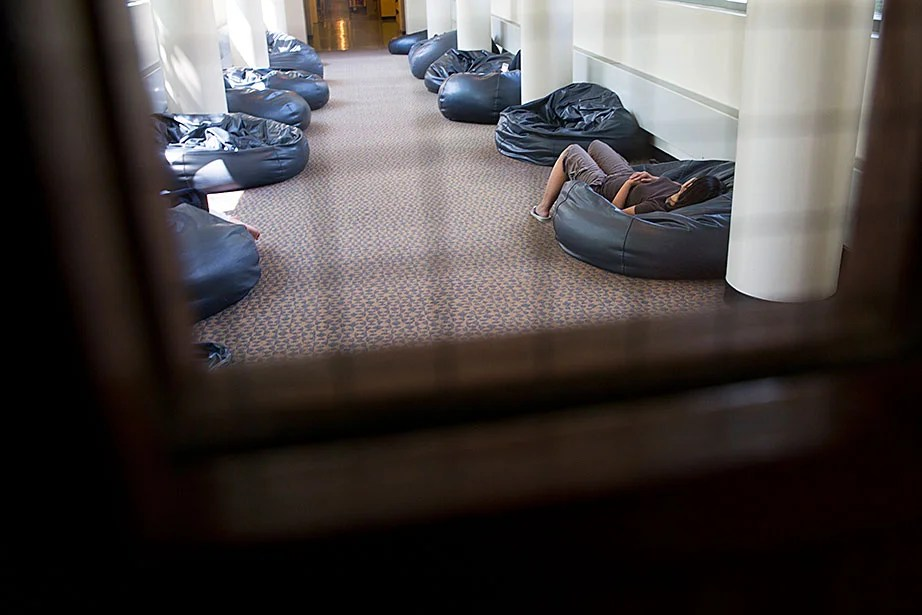 A student rests in a hallway of beanbags at HLS' Langdell Library.