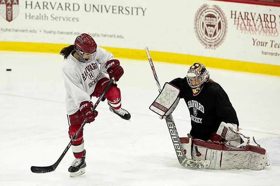 Miye D'Oench '16 high-steps as she flicks a puck toward goalie Emerance Maschmeyer '16 during practice. Jon Chase/Harvard Staff Photographer