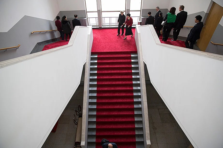 Chen Xu (right) and Drew Faust walk down a grand staircase at Tsinghua University.