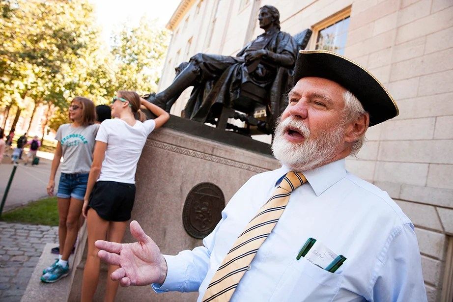 Vincent Dixon, the tour guide for Cambridge Advantage Tours, speaks about his favorite campus facts and tour questions. Dixon is an alumni from the Harvard Extension School and Harvard Graduate School of Education. He is pictured in Harvard Yard by the John Harvard Statue at Harvard University. Stephanie Mitchell/Harvard Staff Photographer
