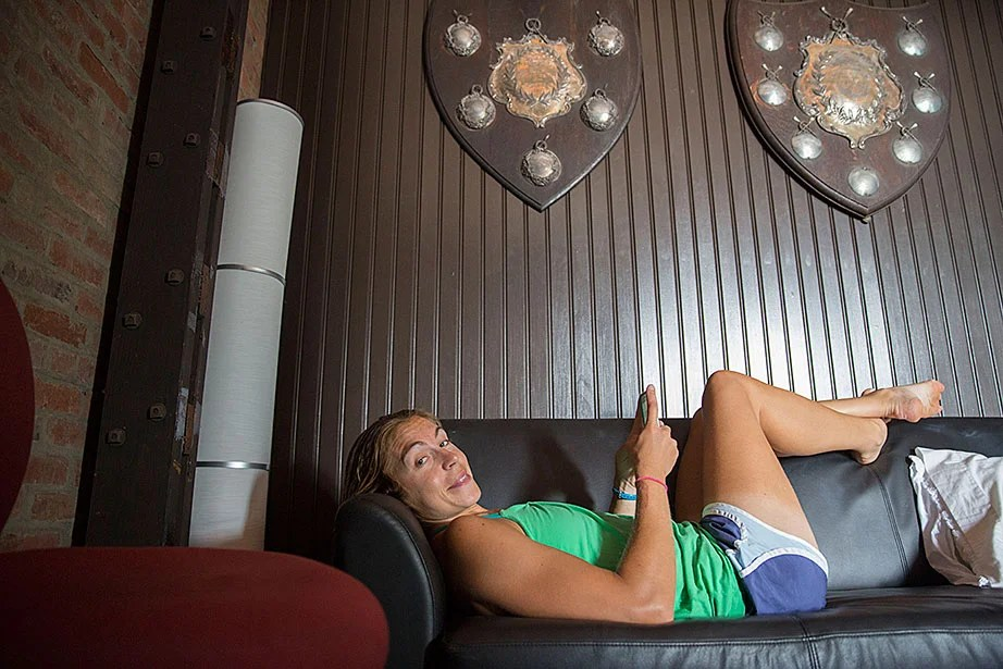 Princeton University rower Gevvie Stone, who is in training for the Olympics, rests in a team room beneath historical trophies.