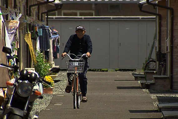 "A man who was evacuated from his home after the Fukushima disaster rides his bike through the Haramachi Temporary Housing. He returns to his abandoned home ""about every other day,"" he says in the film. ""It's not like I do anything special here. I'm just home."" A man who was evacuated from his home after the Fukushima disaster rides his bike through the Haramachi Temporary Housing. He returns to his abandoned home ""about every other day,"" he says in the film. ""It's not like I do anything special here. I'm just home."" Courtesy of Peter Galison and Robb Moss"