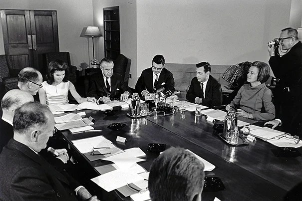 First lady Jacqueline Kennedy presides over the first-ever IOP Senior Advisory Committee meeting. Starting just to Kennedy's right, going clockwise: Nathan Pusey, president of Harvard University,  Kennedy, W. Averell Harriman, chairman, IOP Senior Advisory Committee, Michael Forrestal,executive secretary, IOP Senior Advisory Committee, Richard Neustadt, director, Institute of Politics, Katharine Graham, member, IOP Senior Advisory Committee.