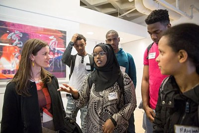 """Julia Kemp (left),  associate director of The Arthur Rock Center for Entrepreneurship, said the Harvard event was """"all about discovery.""""  Kemp greeted Brighton High School students Hibo Moallim (center) and Rahwa Gidey (far right) at the Harvard Innovation Lab for the New Venture Competition."""
