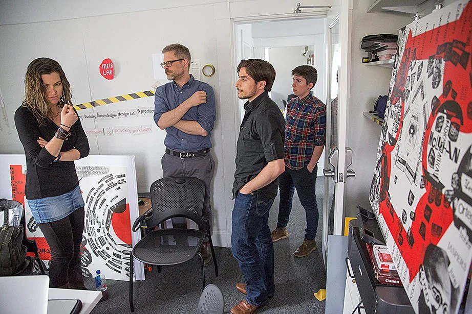 """Sarah Newman (from left), Matthew Battles, Cristoforo Magliozzi, and Jessica Yurkofsky discuss their work inside the metaLAB office/studios. """"With digital technology roiling education, publishing, and visual culture, the arts and humanities sometimes seem imperiled, even under assault. But Harvard's metaLAB doesn't see things that way,"""" says Battles."""