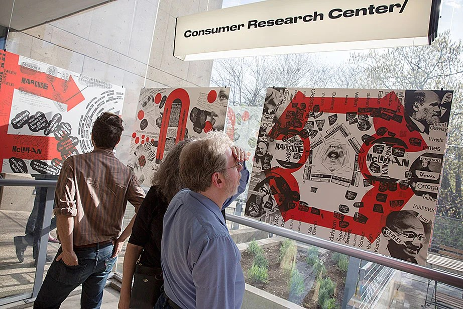 "Audience members look through books at the exhibition and release of an expanded edition of ""Blueprint for Counter Education"" at the Consumer Research Center/bookshop at the Carpenter Center."