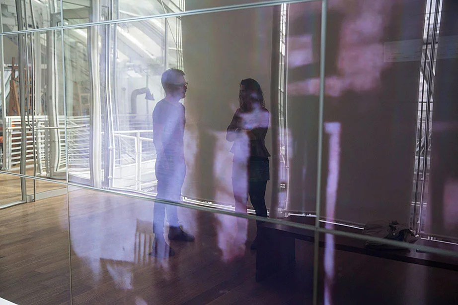 "Matthew Battles and Sarah Newman are framed by photographs displayed in the reflective surface of the video screen used for ""Your Story Has Touched My Heart."" The premiere screening and artist talk took place May 25 with guest art historian Kate Palmer Albers."