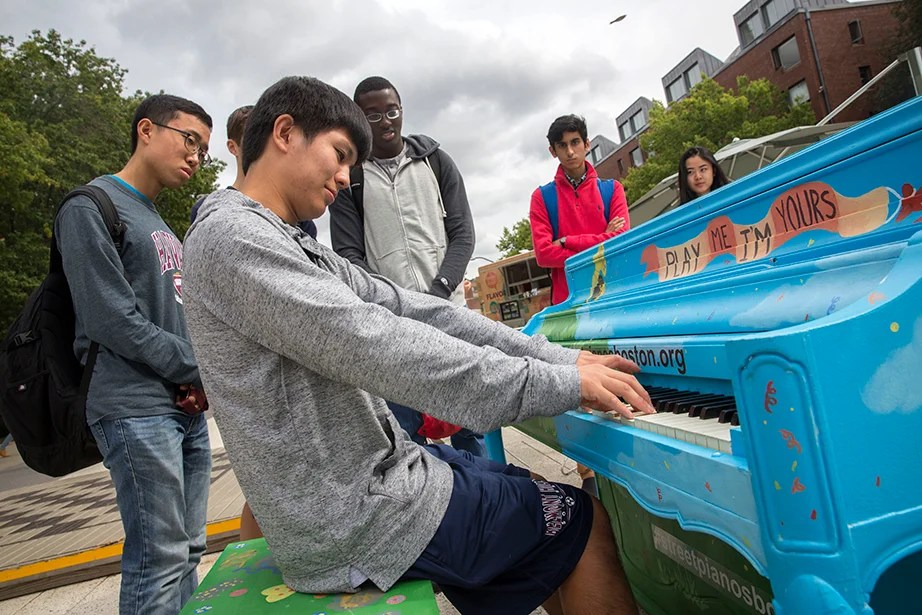 On the Science Center Plaza, master pianist George Hu '20 plays for his friends, Jonathan Suh '20 (from left), Michael Gaba '20, Arjun Mirani '20, and Elizabeth Yeoh-Wang '20, a joint Harvard/New England Conservatory concentrator. Harvard Common Spaces presented the piano as part of Street Pianos Boston 2016 in conjunction with Celebrity Series of Boston. Kris Snibbe/Harvard Staff Photographer