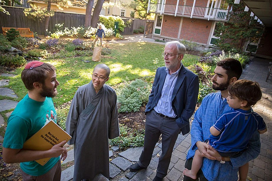 HDS student Daniel Kraft (from left), the Ven. Changshen Shi, CSWR Director Francis Clooney, Ph.D. candidate Seth Powell, and Powell's 2-year-old son, Ruben, talk in the center's courtyard. By facilitating connections with the larger Harvard community and beyond, the center convenes conversations about cutting-edge research.