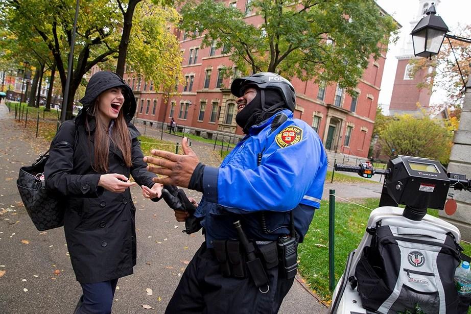 In Harvard Yard Lender shares a laugh with Josiah Christian of the Harvard University Police Department.