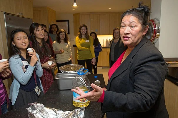 Faith Pak '19 (left) and other Pforzheimer House members listen as Wampanoag chef Sherry Pocknett explains how some of the ingredients used in traditional Native American cuisine were gathered and prepared.