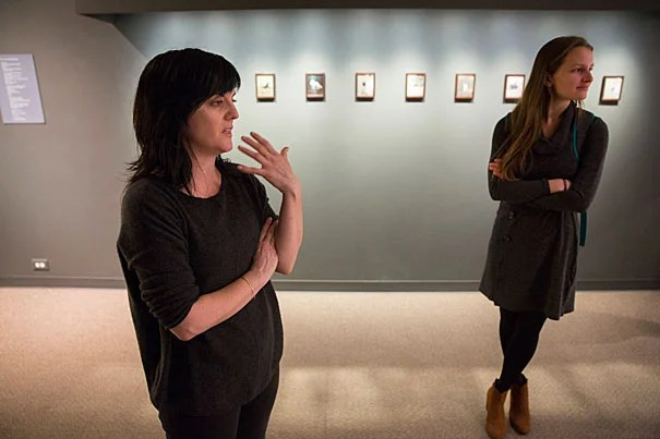 """Visual artist Christina Seely, explains her Harvard Museum of Natural History exhibition on extinction, as seen through an artist's lens, called """"Next of Kin"""". during a staff preview on Friday. On the right is Clara Chaisson, a Boston-based writer and Earthwire's associate editor. Kris Snibbe/Harvard Staff Photographer"""