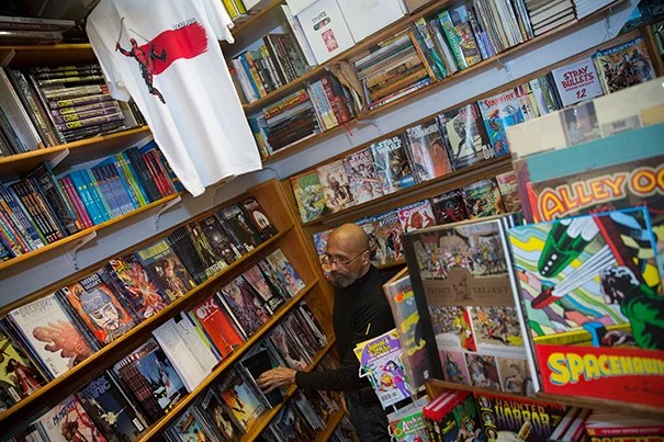 """As part of a student column about """"The Hidden Spots of Harvard Square: A Student's Guide"""" the Million Year Picnic comic book store was featured. Employee, Michael Phillips stocks the shelves inside the store. Kris Snibbe/Harvard Staff Photographer"""