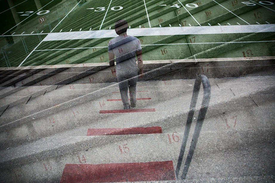 A solitary runner gazes across Harvard Stadium as he climbs and descends the steps.
