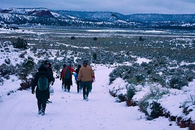 Harvard students leave cars on the paved road to hike into the Clark family homestead in Navajo, N.M.