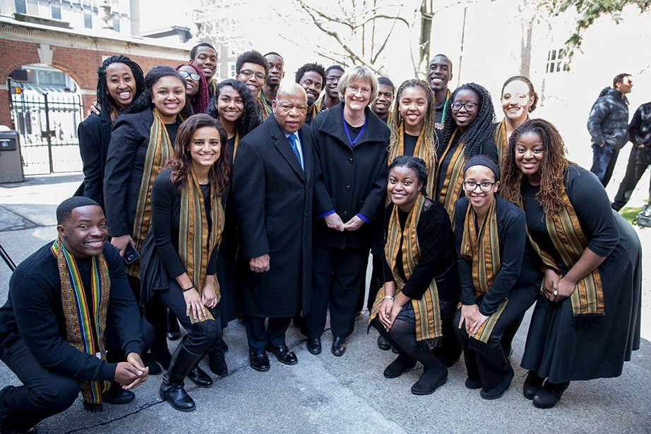 "Unveiling a plaque to honor four enslaved people who lived and worked at Wadsworth House—Titus, Venus, Bilhah, and Juba—U.S. Rep. John Lewis and President Faust are pictured here in April 2016 with the Harvard Kuumba Singers. ""The past never dies or disappears"" Faust wrote in a Harvard Crimson Op-Ed published in advance of the unveiling. ""It continues to shape us in ways we should not try to erase or ignore. In more fully acknowledging our history, Harvard must do its part to undermine the legacies of race and slavery that continue to divide our nation."" Rose Lincoln/Harvard Staff Photographer"