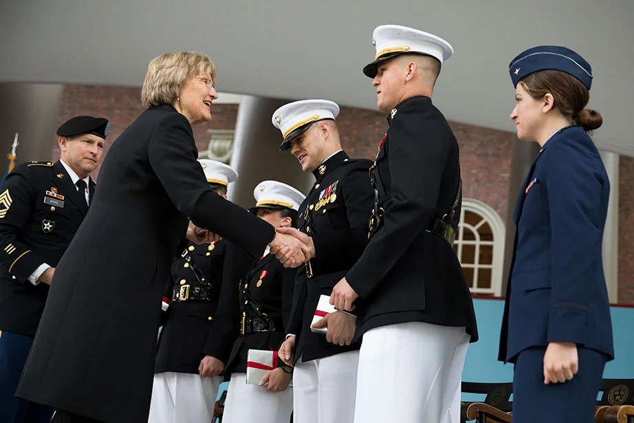"""President Faust congratulates seniors during the ROTC Commissioning Ceremony for the Class of 2014 in Tercentenary Theatre. At the return of the Air Force ROTC regiment in 2016, Faust thanked members of the Harvard community who have served in the military, noting what she called a """"commitment to shared values—service, community, inclusion, and opportunity."""" Stephanie Mitchell/Harvard Staff Photographer"""