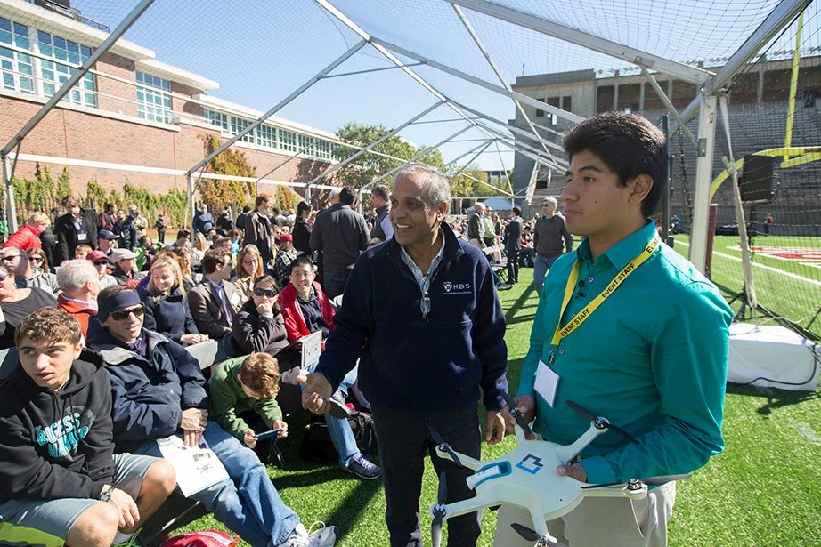 "During ""Making Robotics Fly,"" an event at Harvard Stadium that was part of the Boston-wide ideas festival HUBweek in the fall of 2015, John Aleman of the drone company CyPhY leads a demonstration for Krishna Palepu (left), the Ross Graham Walker Professor of Business Administration. The University anticipates deep and broad collaboration in engineering and entrepreneurship from a growing partnership between HBS and SEAS. Kris Snibbe/Harvard Staff Photographer"