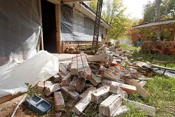 A man clears rubble in Sparks, Okla., following two earthquakes in 24 hours in November 2011. The area is home to thousands of fracking wells.