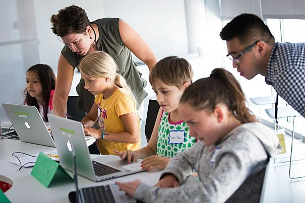 Students Eva Lynch (from left), Abigail Hill, Sarah Kohl, and Grace Hammack get a lesson in creative coding from Irina Uk and Terry Lee.