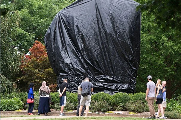 The covered statue of Confederate Gen. Robert E. Lee draws onlookers in Emancipation Park in Charlottesville, Va.