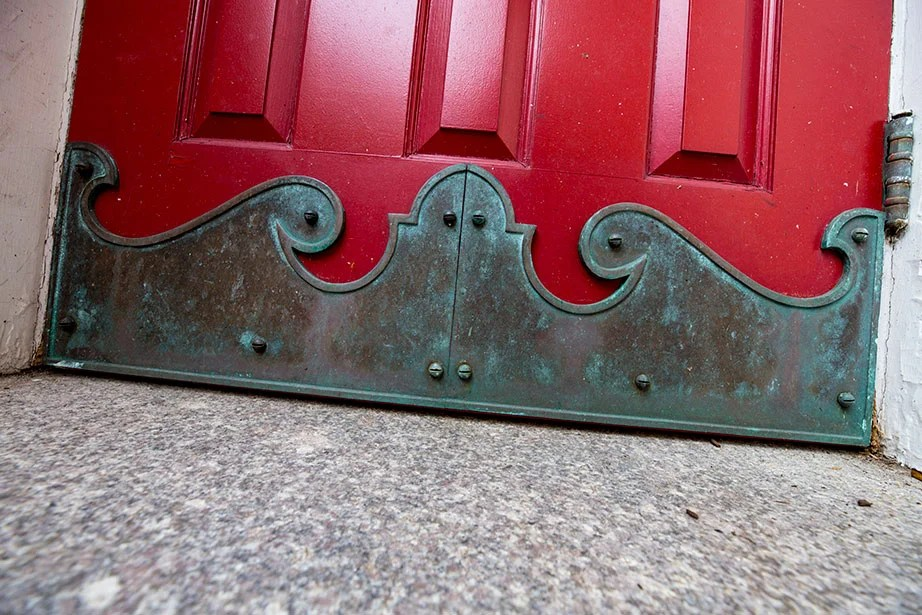 Detail of a brass wave on the bottom of a door in the courtyard.