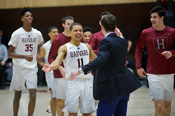 A jubilant Bryce Aiken '20 (center) embraces assistant coach Brian Eskildsen after sinking the winning 3-pointer with seconds to go in overtime, capping a thrilling 70-67 victory over UMass.