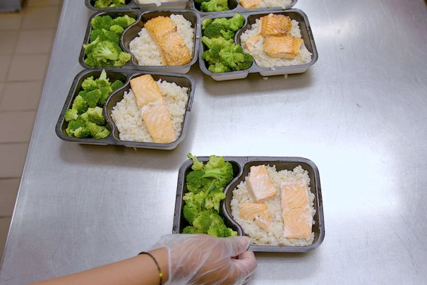Individual meals of salmon, rice, and broccoli.