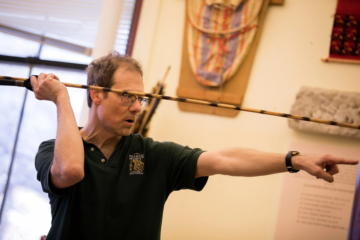 During Wintersession, students learn to make and use the technology that revolutionized human life. The atlatl, or spear-thrower, is a 10,000-year-old tool developed independently across the globe by cultures from the Arctic to New Zealand. The workshop takes place in the Peabody Museum at Harvard University. Andrew Majewski (pictured), the workshop instructor, demonstrates how to throw an atlatl during the workshop.