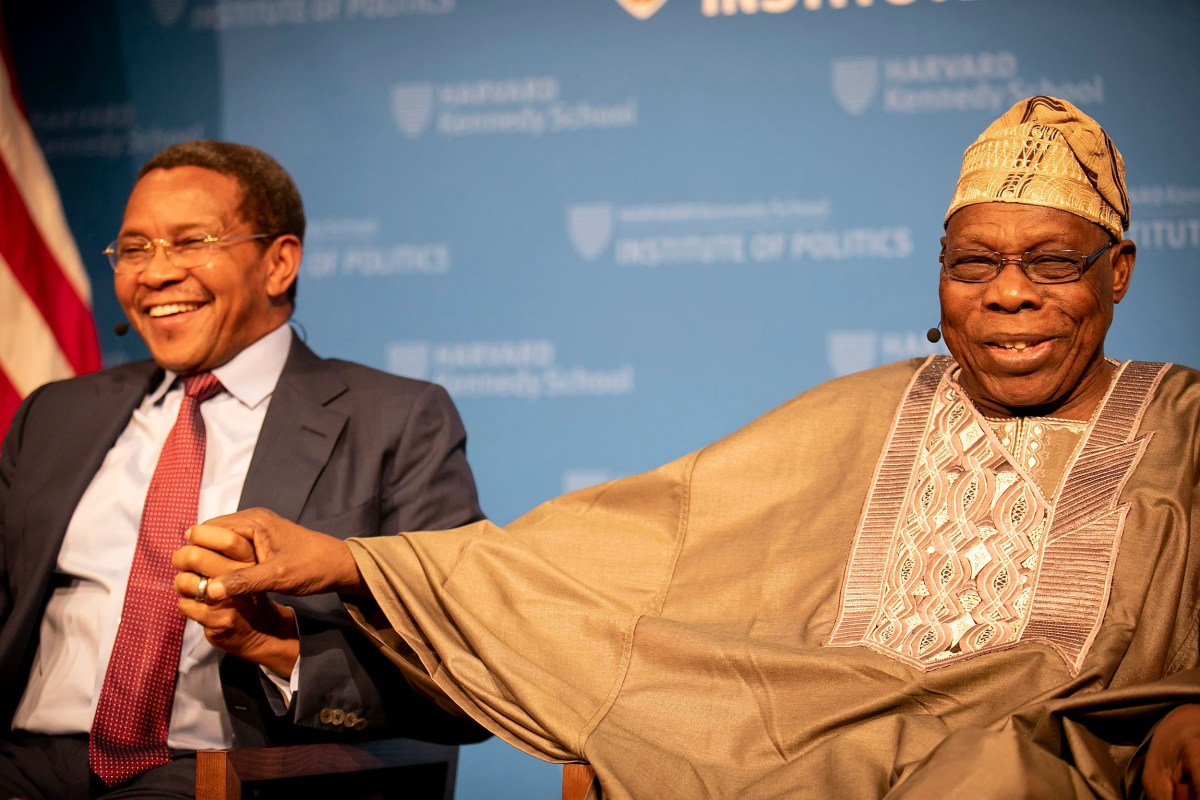 Former leaders Jakaya Mrisho Kikwet of Tanzania (left) and Olusegun Obasanjo of Nigeria take one another by the hand as they share a laugh during a Kennedy School panel on Africa's future.