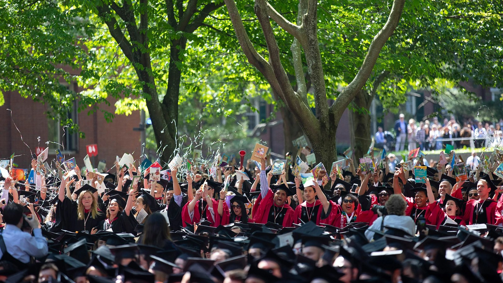 Harvard graduates wave books.