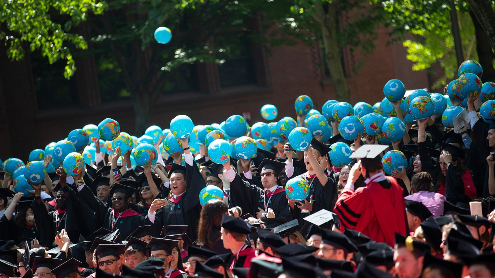 Graduates let inflatable globes loose.