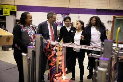 Harvard President Larry Bacow visits the International Technology Academy in Pontiac, Mich. Harvard Graduate School of Education Dean Bridget Terry Long (from left) and Bacow speak with students Haitau Yang, Darcy Mendoza, and Rebecca Murray in the robotics lab of the school.