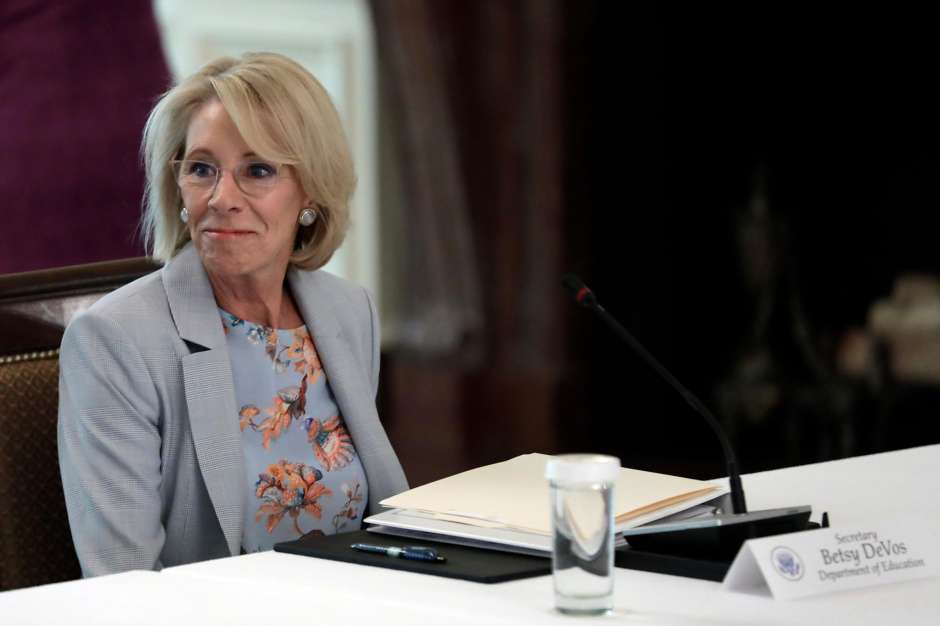 Betsy DeVos sitting at a table for a meeting