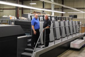 Battlefield Graphics' Matt Theoret, Production Manager, and Jerry Theoret, President, with their Heidelberg Speedmaster XL-106-7+L.