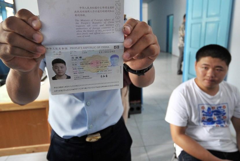 Petugas menunjukkan paspor milik salah seorang warga negara China yang masuk secara ilegal