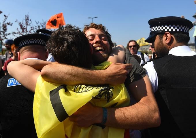 Extinction Rebellion demonstrators hug across a police cordon on Waterloo Bridge