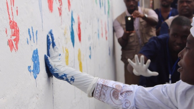 Ms Sankoh adds her handprint to the wall of survivors at the treatment centre