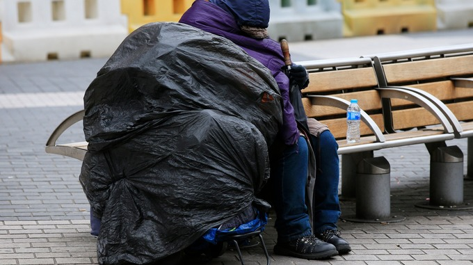 File photo of a homeless woman huddling on a bench