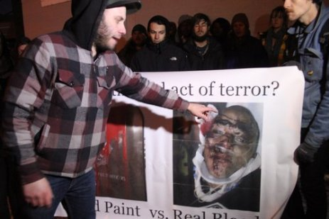 """Denver community gathers to protest felony charges against those who spilled paint on a police memorial monument. The photo is of Landau moments after his 2009 beating by Denver Police. The banner reads, """"Which is the Real Act of Terror?"""""""