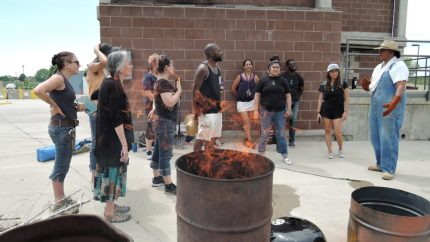 Flames temporarily escape the biochar barrel before being control with a lid