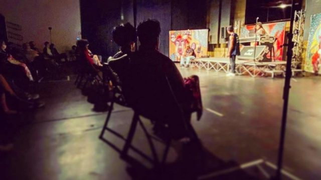 20 audience members in groups of 2 or three watching a socially distanced theatrical performance at The Peoples Building in Aurora, CO