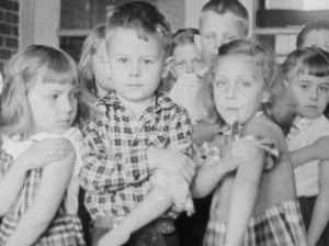 Black and white image of children showing their upper biceps.