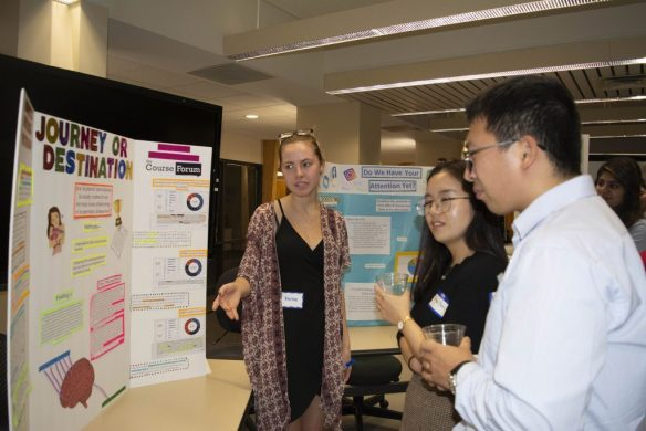 A student explains her poster to two visitors